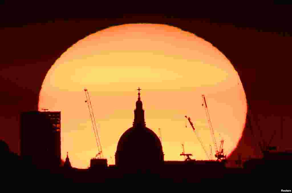 The dome of St. Paul's Cathedral and construction cranes are silhouetted by the rising sun at dawn in London.