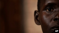 FILE - a South Sudanese refugee and 32-year-old mother, who was raped for several days by a group of soldiers before she was allowed to leave, stands by a window at a women's center.