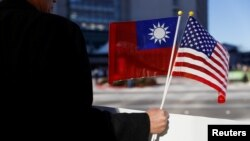 FILE - A demonstrator holds flags of Taiwan and the United States in support of Taiwanese President Tsai Ing-wen during an stopover after her visit to Latin America in Burlingame, Calif., Jan. 14, 2017.