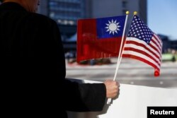 FILE - A demonstrator holds flags of Taiwan and the United States in support of Taiwanese President Tsai Ing-wen during a stopover after her visit to Latin America in Burlingame, Calif., Jan. 14, 2017.