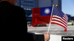 A demonstrator holds flags of Taiwan and the United States in support of Taiwanese President Tsai Ing-wen during an stop-over after her visit to Latin America in Burlingame, California, U.S., January 14, 2017.