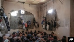 FILE -In this July 18, 2017 file photo, suspected Islamic State members sit inside a small room in a prison south of Mosul.