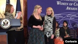Arbana Xharra, 2015 Women of Courage Award recipient, accepts her award from U.S. Ambassador-at-Large for Global Women's Affairs Catherine Russell.
