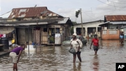 지난달 홍수로 범람한 거리를 걷고 있는 나이지리아 남서부 라고스 주 이코로두의 주민들.