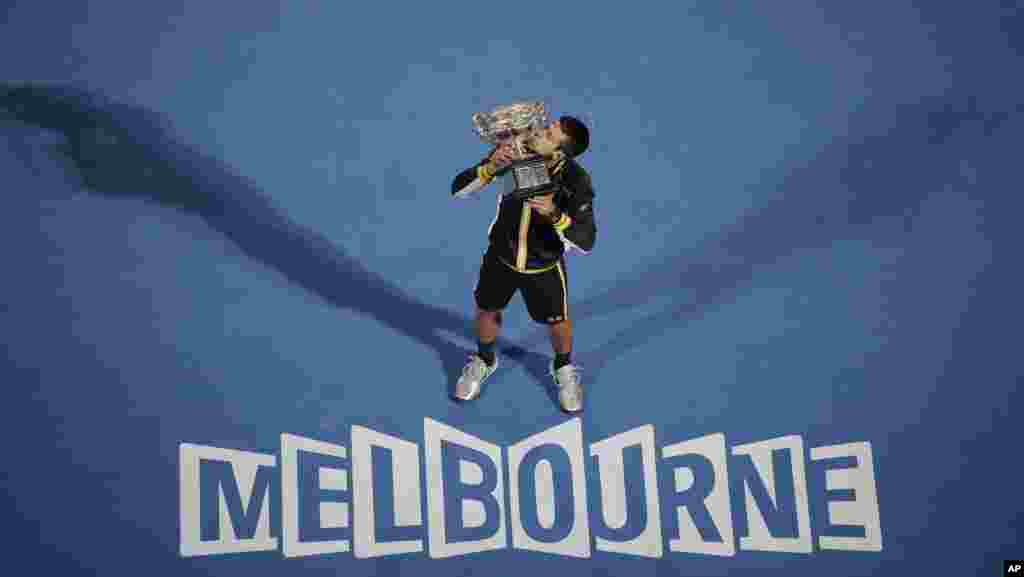 Serbia's Novak Djokovic kisses his trophy after defeating Britain's Andy Murray in the men's final at the Australian Open tennis championship in Melbourne, Australia.