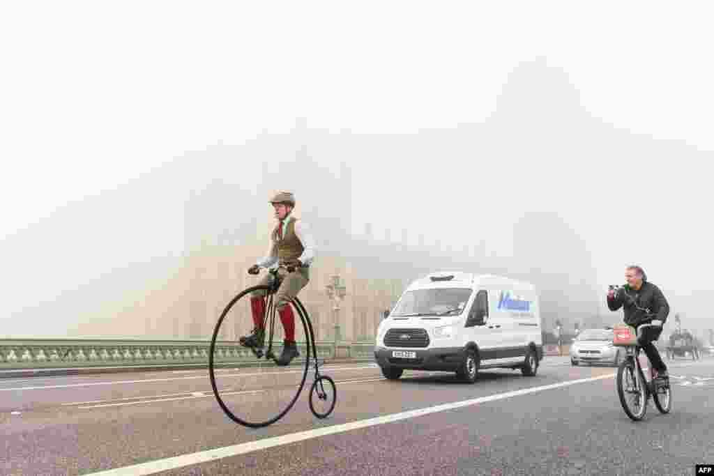 """Seorang laki-laki naik sepeda antik Penny Farthing melewati gedung parlemen di Westminster, tidak lama setelah kompetisi """"Balap Mobil Veteran"""" ke -119 dimulai dari Taman Hyde di London menuju Brighton di Inggris selatan."""