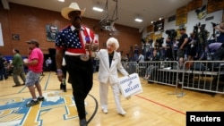 John Goodie (L) accompanies supporter Jerry Emmett before a campaign rally by U.S. Democratic presidential candidate Hillary Clinton at Carl Hayden Community High School in Phoenix, Arizona, March 21, 2016.