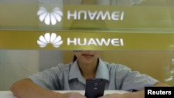 A sales assistant looks at her mobile phone as she waits for customers behind a counter at a Huawei booth in Wuhan, Hubei province, China.