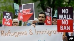 Para pengunjuk rasa mengusung poster dalam sebuah unjukrasa menentang larangan perjalanan yang diperbaharui oleh Presiden Donald Trump di luar gedung pengadilan federal di Seattle, hari Senin, 15 Mei 2017 (foto: AP Photo/Ted S. Warren)