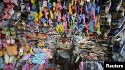 Seorang pedagang sepatu di Taiyuan, propinsi Shanxi sedang menghitung uang di tokonya (13/7). Pertumbuhan ekonomi Tiongkok jatuh ke tingkat terendah dalam tiga tahun akibat ketidakpastian perekonomian global.