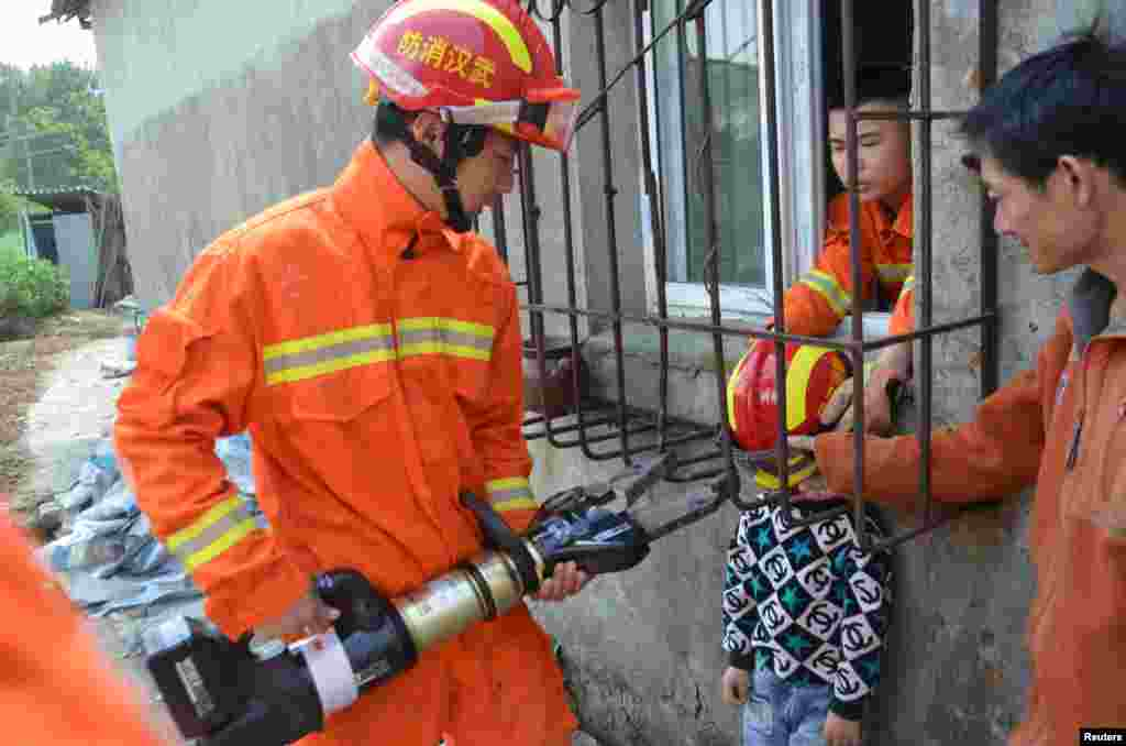 Firemen rescue a boy whose head is stuck between protective bars outside a window in Wuhan, Hubei Province, China.