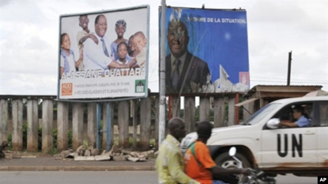 A UN vehicule passes billboards for the presidential electoral campaign on a moped in Bouake, 27 Oct 2010