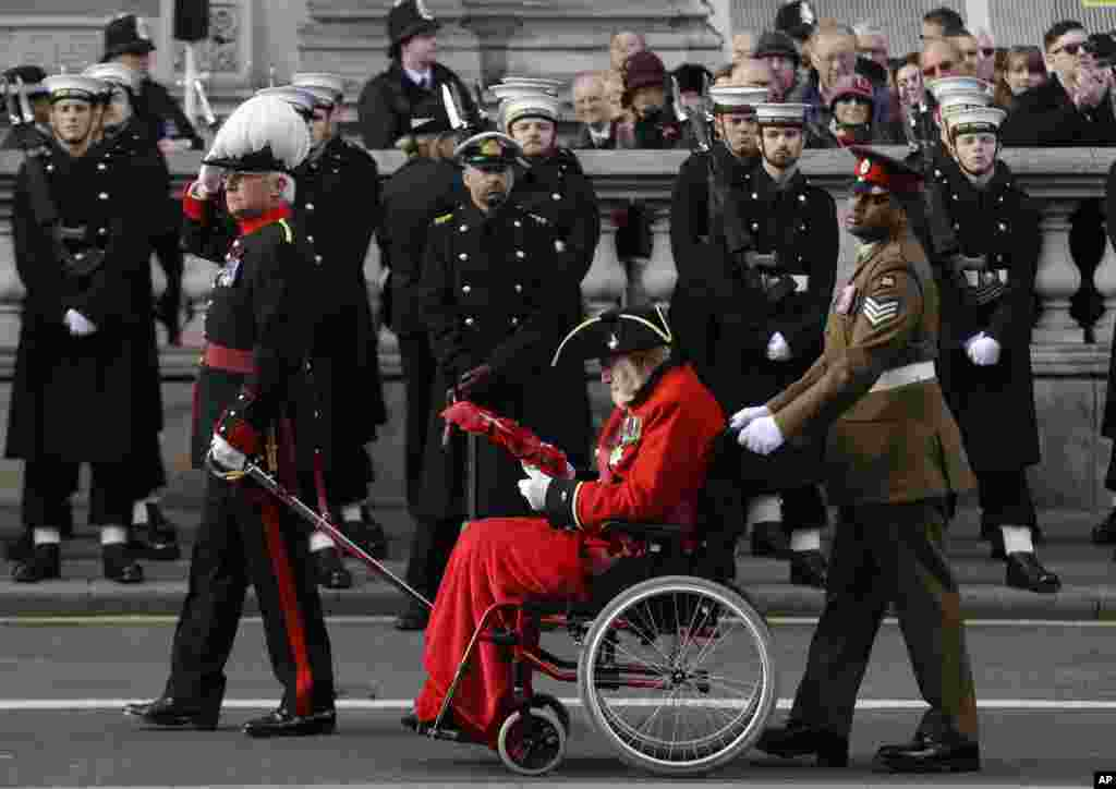 Sargent Johnson Beharry VC, wheels a Chelsea Pensioner past the Cenotaph as he gets ready to hand over his wreath during the Remembrance Sunday service at the Cenotaph in London.