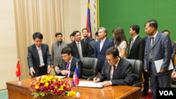 Chairman of Cambodia's border committee, Var Kim Hong (right) and Ho Xuan Son, Vietnamese Deputy Foreign Minister sign the agreement following a three-day meeting at the Council of Ministers in Phnom Penh, Cambodia, Thursday, July 09, 2015. (Neou Vannarin/VOA Khmer)