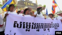 "Land grabbing victims mark the 29th World Habitat Day by demanding a speedy solution to their problems. Holding a banner that reads ""Voices of the Urban Poor"", they walked to the National Assembly in Phnom Penh to submit a petition to the government. (VOA / S. Heimkhemra)"