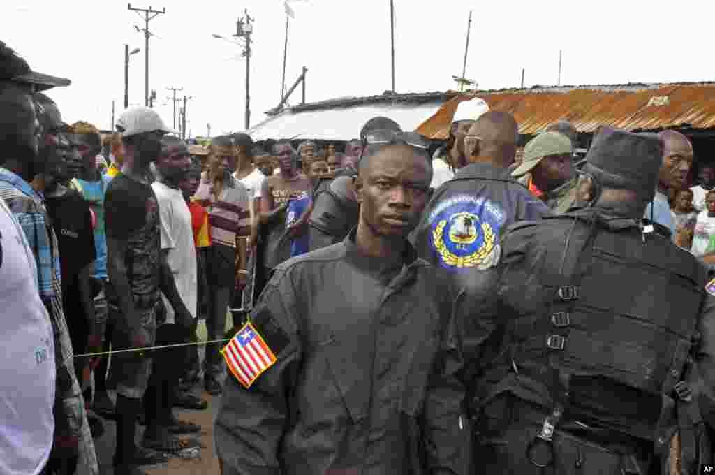 Liberian policemen (right) speak with residents of the West Point area to calm them down as they wait for a second consignment of food from the Liberian Government, at the West Point area, Monrovia, Liberia, Aug. 22, 2014.