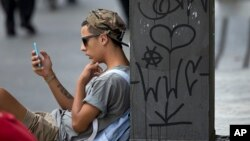FILE - A young man checks his cell phone in Sao Paulo, Brazil, Dec. 17, 2015. A judicial order issued earlier this week left 100 million Brazilians without access to the popular WhatsApp messaging platform for 72 hours.