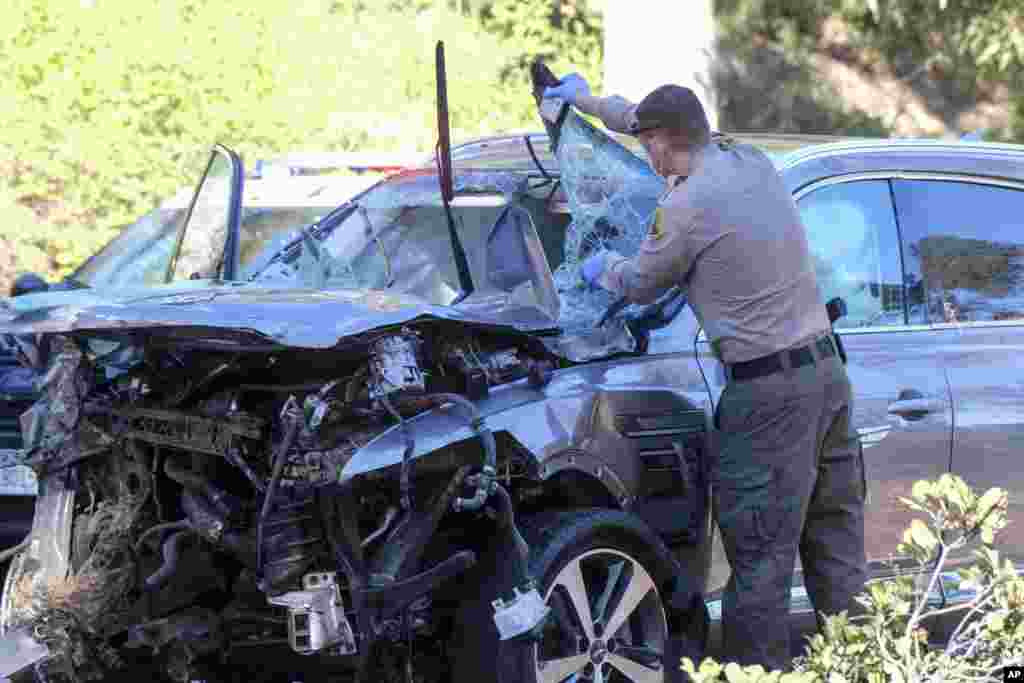 A law enforcement officer inspects a damaged vehicle following a rollover accident involving golfer Tiger Woods, Feb. 23, 2021, in the Rancho Palos Verdes area of Los Angeles, California.Woods suffered leg injuries in the one-car accident and was undergoing a medical operation, officials and his manager said.