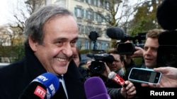 FILE - UEFA President Michel Platini smiles as he arrives for a hearing at the Court of Arbitration for Sport (CAS) in Lausanne, Switzerland, Dec. 8, 2015.