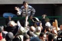 Wa Tunisia wakisubiri mkate nje ya duka mjini Tunis Jumapili Januari 16 2011, baada ya ghasia zilizomsababisha rais Ben Ali kuikimbia nchi.