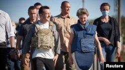 Presiden Ukraina Volodymyr Zelensky dan Presiden Swiss Simonetta Sommaruga saat mengunjungi wilayah bekas pertempuran antara pasukan pemerintah Ukraina dan pemberontak yang didukung Rusia, di permukiman Stanytsia Luhanska, Ukraina, 23 Juli 2020. (Foto: R