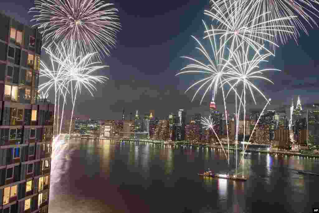 With the New York City skyline in the background fireworks explode during an Independence Day show over the East River, July 4, 2017.