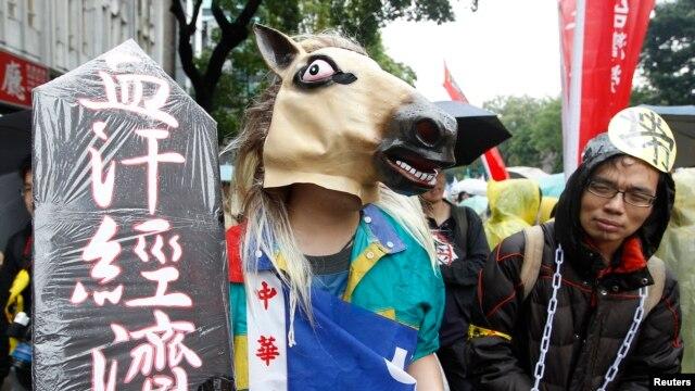 Seorang peserta aksi demo Hari Buruh (May Day) menggunakan topi kuda dan rantai dalam pawai yang melintasi gedung Eksekutif Yuan di pusat kota Taipei, Taiwan (1/5).
