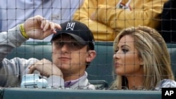 FILE - Cleveland Browns quarterback Johnny Manziel, left, sits with Colleen Crowley during a baseball game in Arlington, Texas, April 14, 2015.