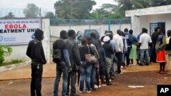 Para petugas kesehatan bersiap memasuki klinik di Monrovia, Liberia Senin (13/10).
