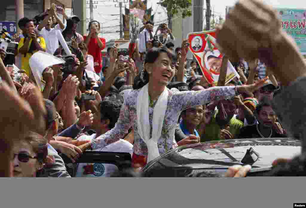 Burma's pro-democracy leader Aung San Suu Kyi greets migrant workers from Burma as she visits them in Samut Sakhon province, Thailand, May 30, 2012.