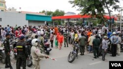 Cambodians gather outside a convenience store where political analyst Kem Ley was gunned down, Sunday July 09, 2016, Phnom Penh, Cambodia. (Leng Len/VOA Khmer)