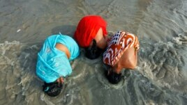 Female Hindu pilgrims take a dip at the confluence of the Ganges river and the Bay of Bengal at Sagar Island, India, January 13, 2012. (Reuters)