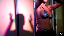 """La silhouette d'une danseuse est aperçue sur un mur derrière une scène lors d'un spectacle de strip-tease à la foire érotique """"Extasia05"""" au centre des expositions Palexpo à Genève, en Suisse, 18 novembre 2005."""