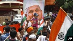 A supporter of anti-corruption activist Anna Hazare, portrait seen, carries a child on his head as he waits along with others outside Tihar prison, where Hazare is presently lodged, in New Delhi, India, August 18, 2011