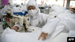Workers sew hazardous material suits to be used in the COVID-19 outbreak at the Zhejiang Ugly Duck Industry garment factory in Wenzhou, China. (Photo by NOEL CELIS / AFP)