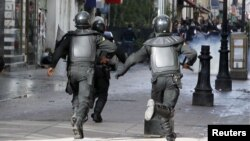 Tunisian riot police run towards protesters during a demonstration in Tunis, February 7, 2013.