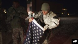 這名駐伊拉克美軍星期天離開伊拉克前折疊好一面美國國旗
