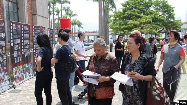 中國大陸遊客在香港閱讀六四文宣 (美國之音記者申華 拍攝))