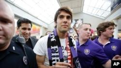 Bintang sepakbola Brazil, Kaka, dikawal petugas keamanan dan polisi tiba di bandar udara internasional Orlando, 2014.