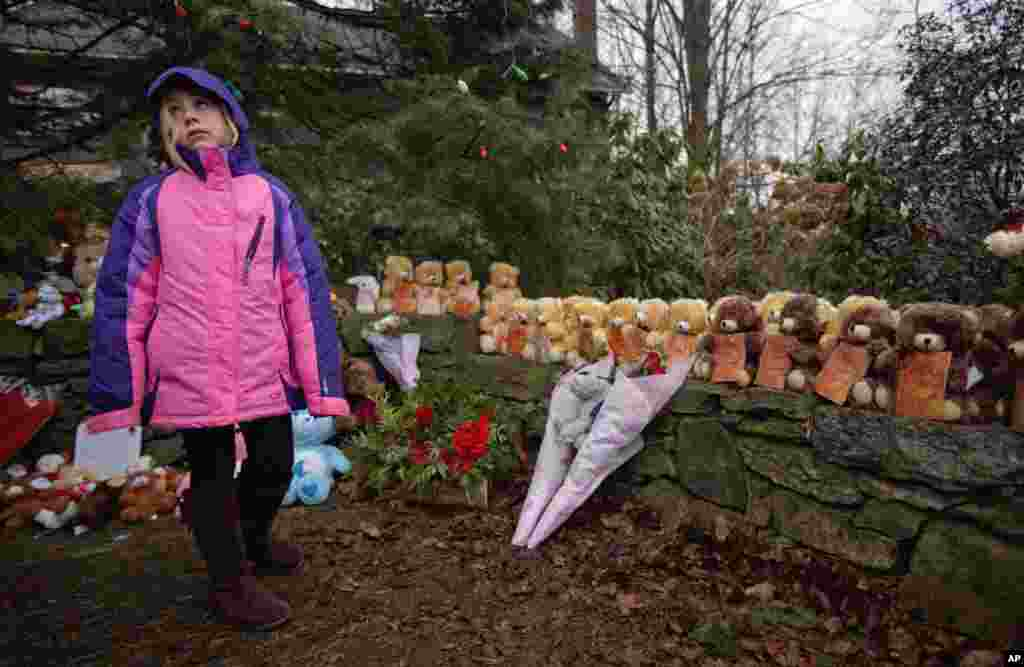 Ava Staiti, 7, of New Milford, Conn., looks up at her mother Emily Staiti, not pictured, while visiting a sidewalk memorial with 26 teddy bears, each representing a victim of the Sandy Hook Elementary School shooting, December 16, 2012, in Newtown, Connecticut.