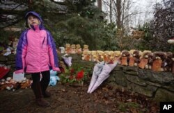 FILE - Ava Staiti, 7, of New Milford, Connecticut, visits a sidewalk memorial with teddy bears representing victims of the Sandy Hook Elementary School shooting in Newtown, Conn., Dec. 16, 2012.