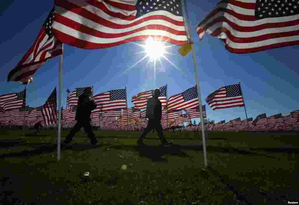 A couple walks through some of the two thousand and thirteen United States flags, that are part of the Aurora Healing Fields to honor veterans, during Veterans Day weekend, Aurora, Illinois, Nov., 10, 2013.