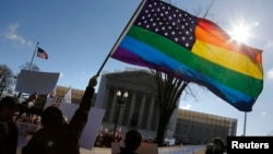 FILE - Gay activists wave a rainbow flag in front of the U.S. Supreme Court in Washington, March 26, 2013.