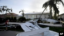 A roof is strewn across a home's lawn as Rick Freedman checks his neighbor's damage from Hurricane Irma in Marco Island, Fla., Sept. 11, 2017.