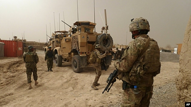 US soldiers keep watch at the entrance of a military base near Alkozai village following the shooting of Afghan civilians allegedly committed by a rogue US soldier in Panjwayi. NATO's International Security Assistance Force said it had arrested a soldier