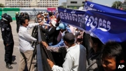 Cambodia land and forest activists stand at a blocked street near the National Assembly, in Phnom Penh, Cambodia, Thursday, May 29, 2014.