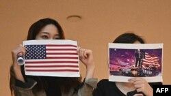 兩名香港女子在一個商場內舉行的抗議中國人大制定港版國安法的集會上手舉美國國旗和川普總統畫像。 (2020年5月28日)