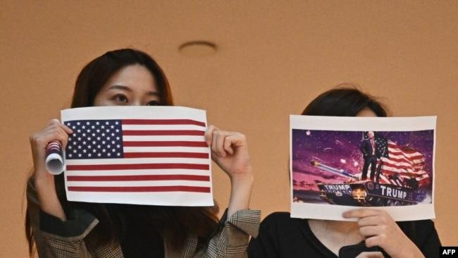 两名香港女子在一个商场内举行的抗议中国人大制定港版国安法的集会上手举美国国旗和川普总统画像。(法新社2020年5月28日)
