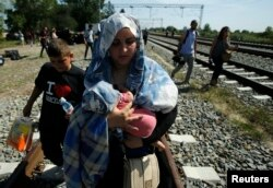 A migrant woman carries a baby as she walks on a railway track near Tovarnik, Croatia Sept. 17, 2015.