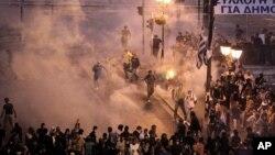 Demonstran di Athena, Yunani bentrok dengan polisi yang menembakkan gas air mata dalam protes menentang kenaikan pajak dan pemotongan anggaran pemerintah (foto: dok).